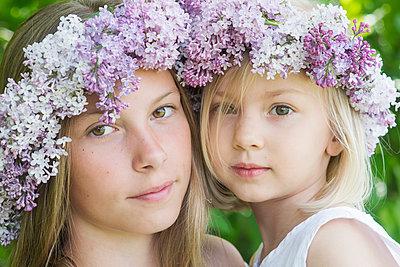portrait of two girls with floral wreaths  - p1323m1575261 von Sarah Toure