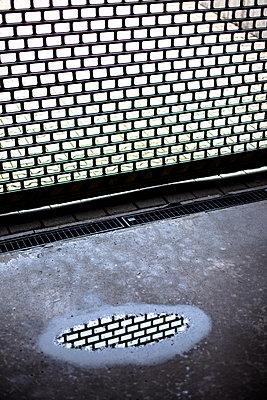 Geschlossenes Rollgitter einer Tiefgarage mit Spiegelung in Pfütze - p795m2087487 von Janklein