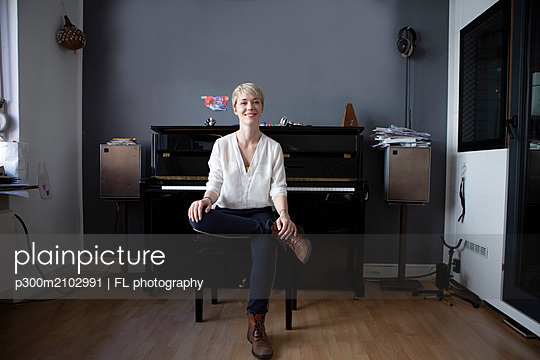 Portrait of relaxed woman sitting in her music room in front of piano - p300m2102991 by FL photography