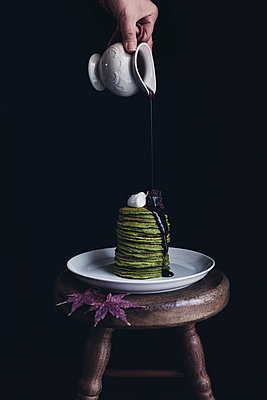 Brown sugar syrup being poured on matcha pancakes in plate on table against black background - p1166m1143001 by Cavan Images