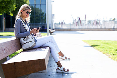 Young businesswoman texting with her mobile phone while sitting on bench - p300m2114581 by Josep Suria
