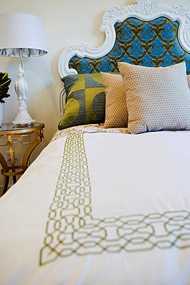 Throw pillows on bed with decorative headboard - p555m738652f by Eric Hernandez