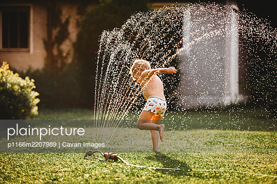 Young white boy running under the water from the sprinkler in garden - p1166m2207989 by Cavan Images
