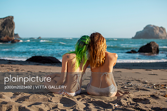 USA, California, West Coast, back view of two young women sitting head to head on the beach - p300m2023492 by VITTA GALLERY