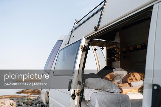 Man relaxing in camping van at lakeshore - p426m2296172 by Maskot