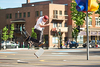 Man doing 360 flip while skateboarding in park, Montreal, Quebec, Canada - p1362m1530059 by Charles Knox