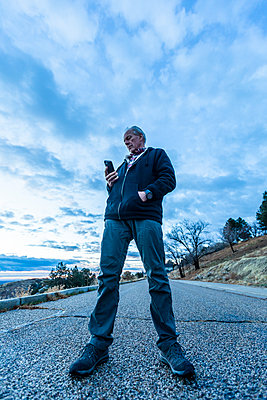 Low angle view of man holding smart phone on road - p1427m2109956 by Steve Smith