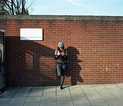 Woman with smartphone leaning against wall - p1462m2146339 by Massimo Giovannini