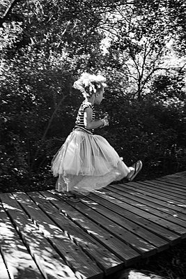 Girl in tulle skirt walks across planked footpath - p1640m2246821 by Holly & John