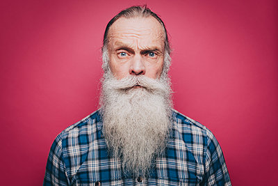 Portrait of confident senior man with long white beard over pink background - p426m1588485 by Maskot