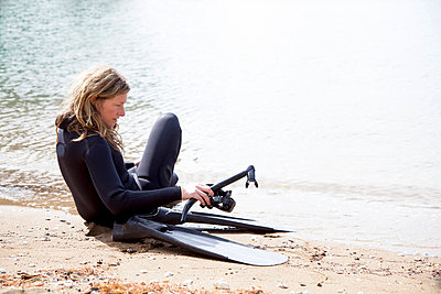 Mid adult female scuba diver preparing to dive on beach - p924m947807f by Axel Bernstorff