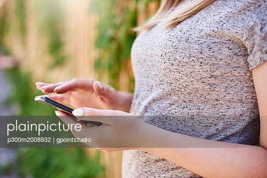 Woman using smartphone, partial view - p300m2008932 von gpointstudio