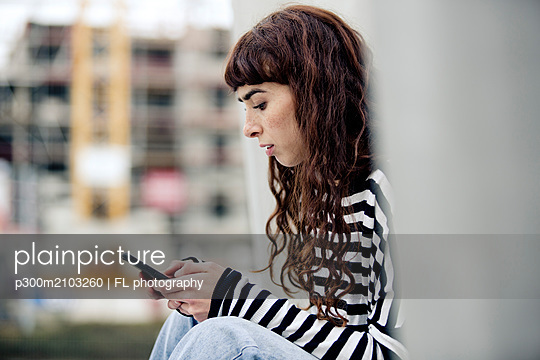 young woman wearing striped shirt, using smartphone - p300m2103260 by FL photography