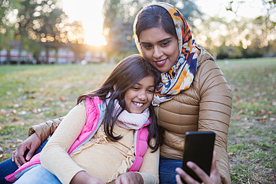 Muslim mother in hijab taking selfie with daughter in autumn park - p1023m2087933 by Tom Merton