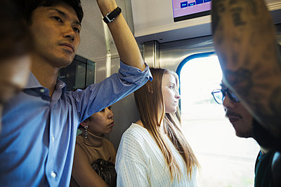 Small group of people standing on a subway train, Tokyo commuters.  - p1100m1531115 by Mint Images