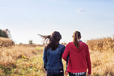 Rear view of sisters walking on grassy field against sky - p1166m1210108 by Cavan Images