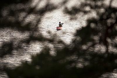 Man fishing from his canoe - p1687m2295144 by Katja Kircher