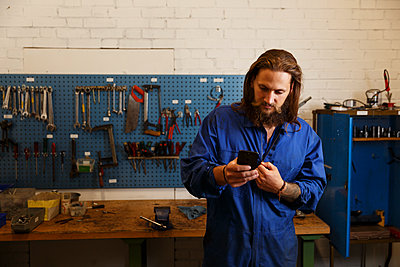Mechanic checks his phone in a workshop in Sweden - p352m2039947 by Christian Ferm