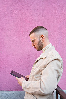 Young man using digital tablet, pink background - p429m2127493 by Francesco Buttitta