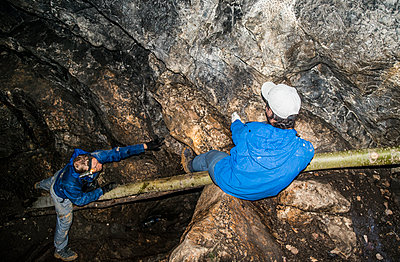 Caucasian climbers exploring rock formation cave - p555m1414469 by Aleksander Rubtsov