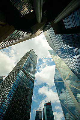 View of modern skyscrapers against cloudy sky in Hong Kong - p623m2294906 by Pablo Camacho