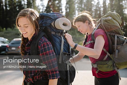 Female backpackers preparing packs in parking lot - p1192m2129244 by Hero Images