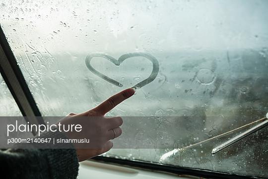 Woman's finger drawing a heart on the window of a van - p300m2140647 by sinanmuslu