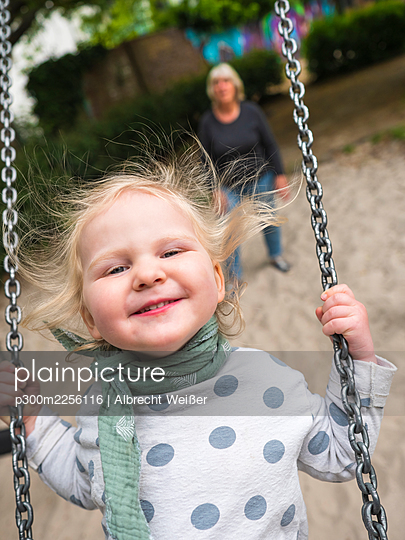 Cheerful girl on swing while grandmother standing at park - p300m2256116 by Albrecht Weißer