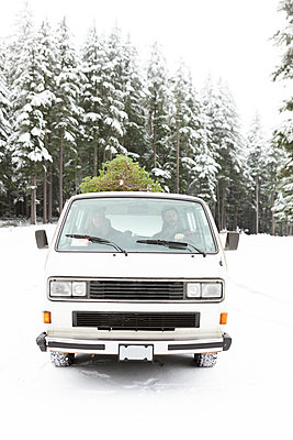 Man and woman driving van on snow covered road with Christmas tree - p1166m2073832 by Cavan Images