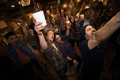 Enthusiastic friends drinking beer and cheering, dancing at music concert party - p1192m1403435 by Hero Images