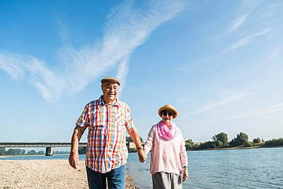 Germany, Ludwigshafen, happy senior couple walking hand in hand at riverside - p300m1068937f by Uwe Umstätter