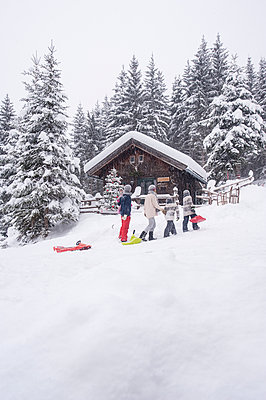 Austria, Altenmarkt-Zauchensee, family with sledges at wooden house at Christmas time - p300m2042009 by Hans Huber