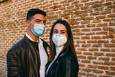 Young couple wearing face mask looking away while standing together against brick wall - p300m2224860 by Andrés Benitez