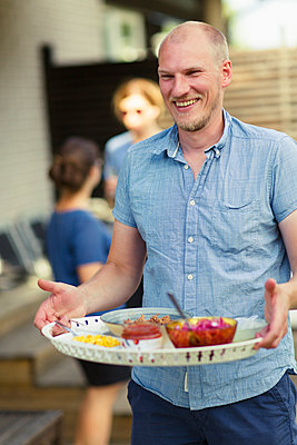 Sweden, Vasterbotten, Man carrying tray with food - p352m1187093 by Jonas Gunnarsson
