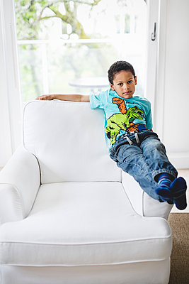 Portrait of boy sitting on handrest of armchair at home - p426m1085424f by Maskot