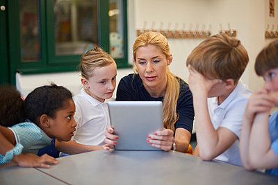 Teacher with schoolgirls and boys looking at digital tablet in classroom at primary school - p429m1547979 by Sydney Bourne