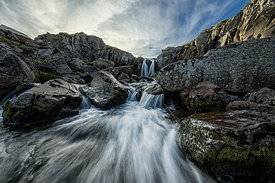 Stream flows over a waterfall and through the rocks along the eastern coast of Iceland; Iceland - p442m1141514 by Robert Postma