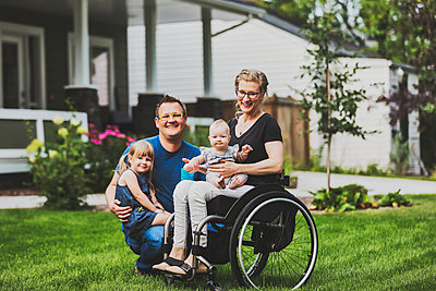 A young family posing for a family portrait outdoors in their front yard and the mother is a paraplegic in a wheelchair; Edmonton, Alberta, Canada - p442m2177329 by LJM Photo