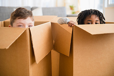 Close up of boys playing in cardboard boxes - p555m1410962 by JGI/Jamie Grill