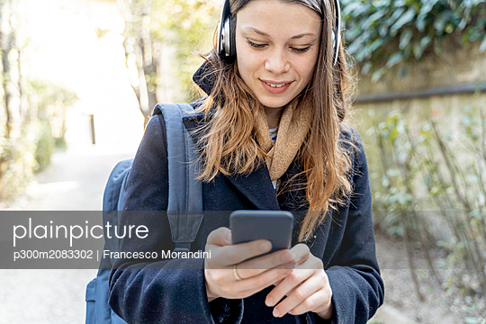 Young woman with headphones, using smartphone, walking in the city - p300m2083302 by Francesco Morandini