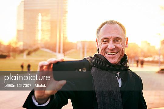 Mann macht ein Selfie in der Stadt - p890m1217307 von Mielek
