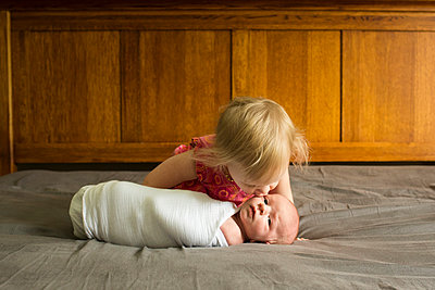 Girl kissing brother lying on bed at home - p1166m1403956 by Cavan Images