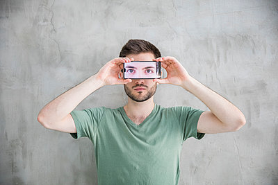 Young man is holding smartphone with his eyes on the display - p276m2110763 by plainpicture