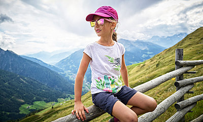 Girl having a break from hiking sitting on a wooden fence, Passeier Valley, South Tyrol, Italy - p300m2155644 von Dirk Kittelberger