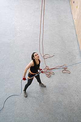 Woman with a rope securing partner on the wall in climbing gym - p300m2170579 by Hernandez and Sorokina