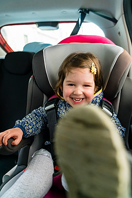 Portrait of laughing little girl sitting on child's seat in car - p300m2189426 by Giorgio Magini