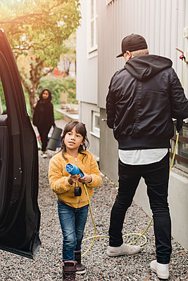 Girl helping father in charging electric car while going for picnic - p426m2194965 by Maskot