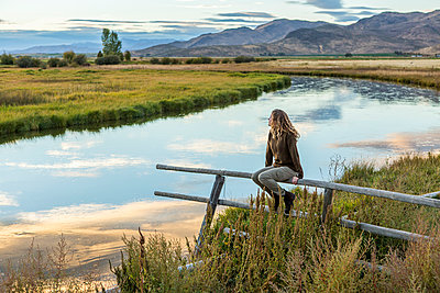 Caucasian woman sitting on wooden fence near mountain river - p555m1302046 by Steve Smith
