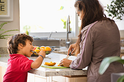 Hispanic mother and son eating fruit in kitchen - p555m1410887 by Sollina Images