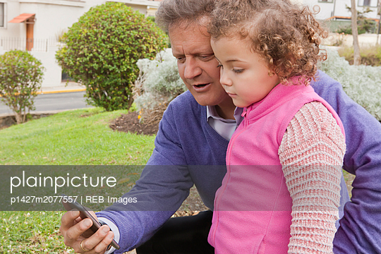 Man sharing smart phone with his daughter - p1427m2077557 by REB Images